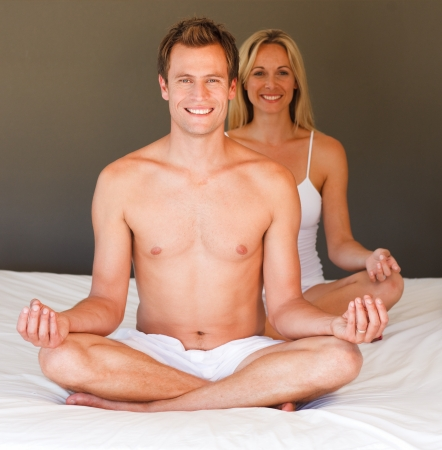 Smiling couple doing exercises on bed photo