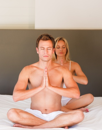 Young couple on budha position on bed Stock Photo - 10114907