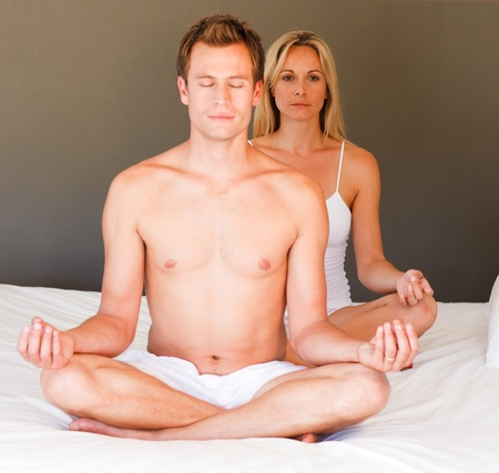 Young girl doing yoga on bed with her boyfriend photo