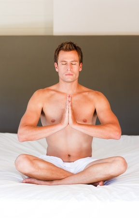 Handsome man meditating on bed with clossed eyes photo