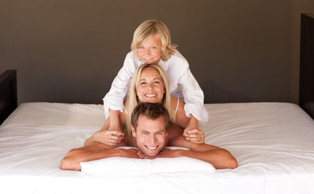 Cute little boy and his parents having fun lying on the bed photo
