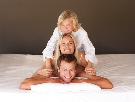 Adorable little boy and his parents having fun lying on the bed photo