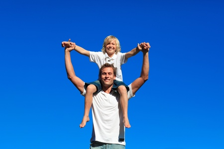 Son sitting on his fathers shoulders photo