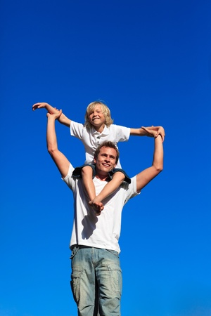 Boy sitting on his fathers shoulders photo