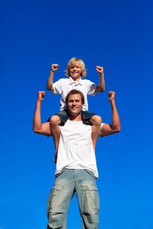 Starke sitzen auf seines Vaters Schultern Sohn