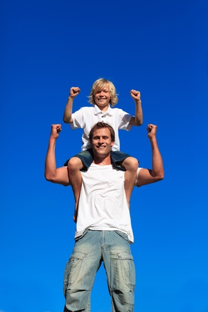 Strong son sitting on his fathers shoulders Stockfoto