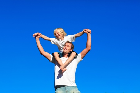 Youth sitting on his fathers shoulders photo