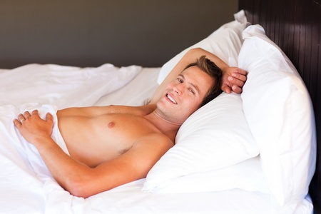Young man relaxing in bed photo