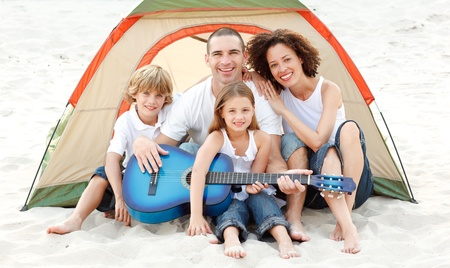 Family camping on beach playing a guitar photo