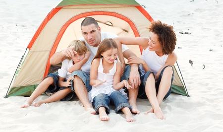 Happy family camping on beach photo