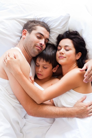 Couple and son sleeping in bed  photo