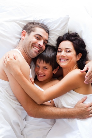 Happy family together in bed  photo