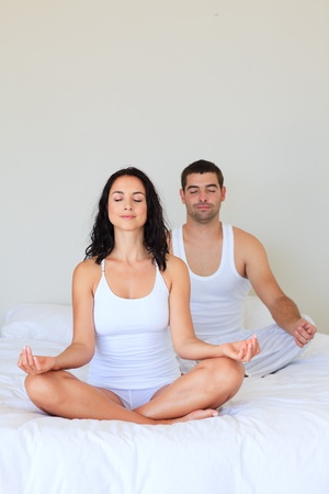 Couple meditating in bed photo