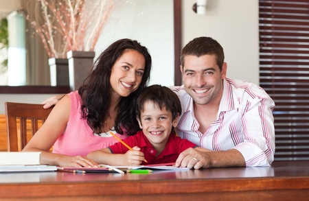 learning by doing: Smiling couple helping his son for homework Stock Photo