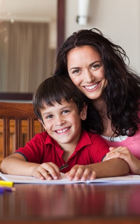 Delighted mother helping his son for homework photo