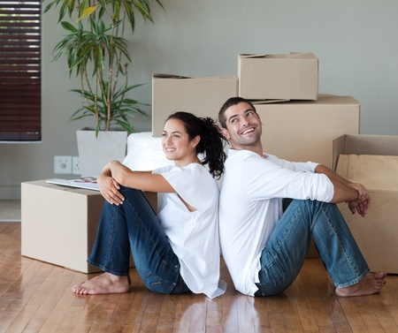 thirty���s: Joyful couple with unpacking boxes moving to a new house Stock Photo