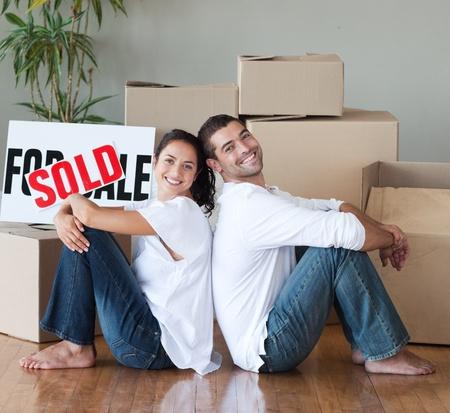 thirty���s: Happy couple with unpacking boxes moving to a new house