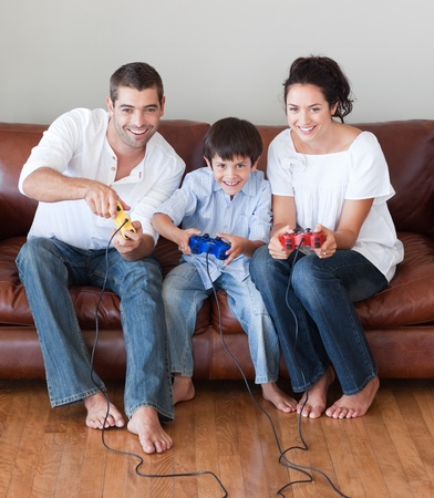Radiant family playing video games in the living-room Stock Photo - 10115506