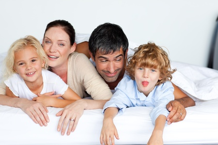 Happy family resting on a bed Stock Photo - 10128486