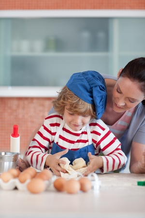 Bright mother and her son baking at home photo