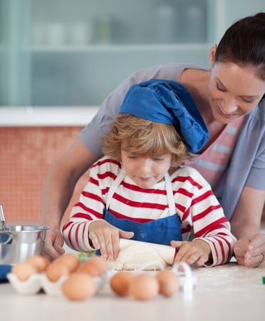 Delighted mother and her son baking at home photo