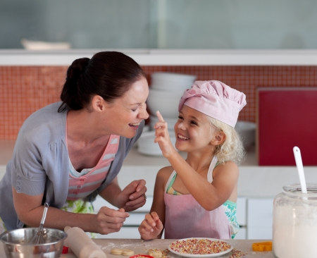 Smiling mother and her daughter baking in a kitchen photo
