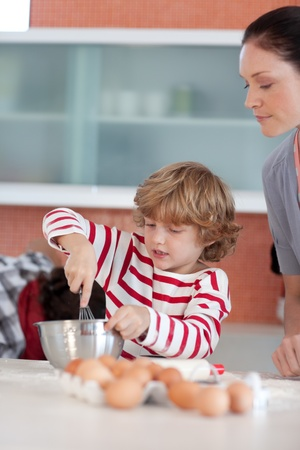 Happy mother baking at ome with her son photo