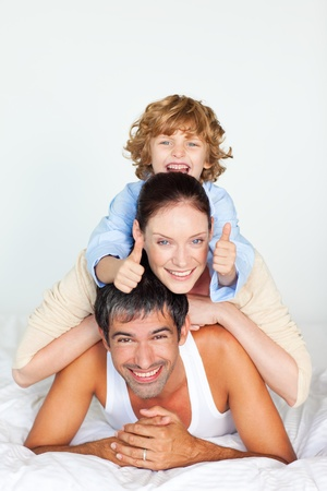 Happy family lying on a white bed Stock Photo - 10115090
