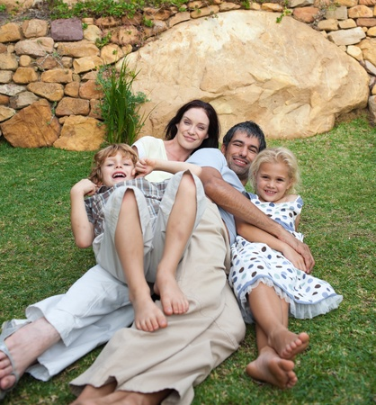Smiling family resting in a garden photo