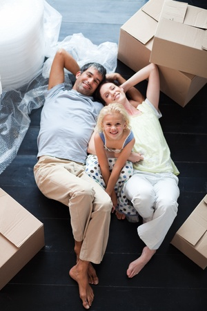 Parents and daughter on the floor with a lot of boxes photo