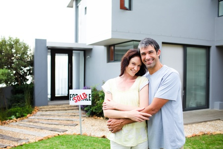 Newlyweds with their new house Stock Photo - 10128315