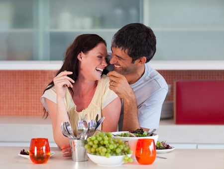 Lovers eating in the kitchen photo