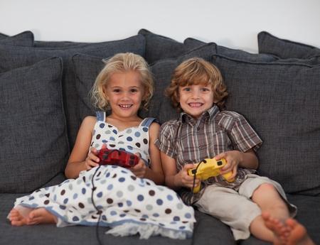 niños jugando videojuegos: Los niños alegres jugando juegos de video en el hogar Foto de archivo