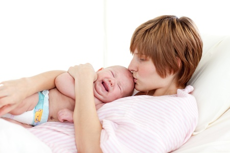 Mother kissing her newborn baby photo