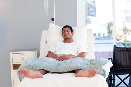 Hispanic patiënt in bed glimlachen naar de camera
