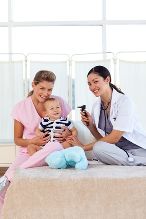 Baby with pediatrician and nurse with copy-space photo