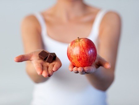 Close-up of woman showing chocolate and apple focus on apple  Stock Photo - 10115182