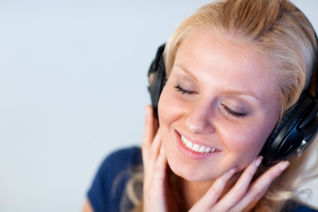 Smiling woman with closed eyes and headphones  photo