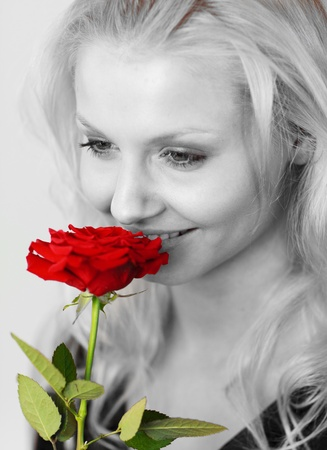 Smiling woman in black and white smelling a red rose  photo