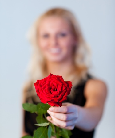 Young woman holding a rose with focus on rose  photo