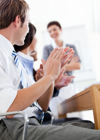 Jolly business people applauding a good presentation photo