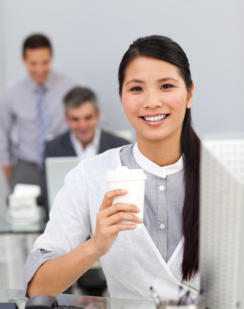 Asian woman drinking coffee in the office photo