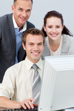 Smiling business people working together with a computer photo