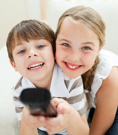 personas viendo television: Lindo hermano y hermana viendo TV Foto de archivo