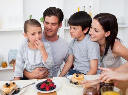 family eating: Sonriendo familia comer panqueques para el desayuno