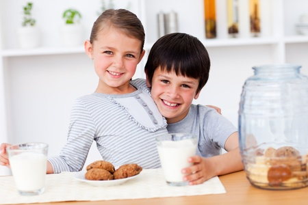 childrens food: Portrait of smiling brother and sister eating biscuits