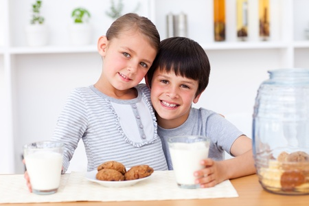 Portrait of happy siblings eating biscuits photo