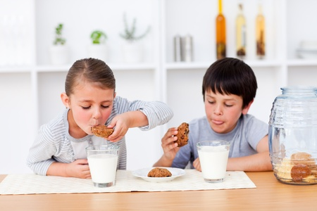 snacking: Happy Siblings eating biscuits and drinking milk