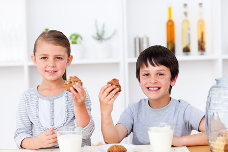 Smiling brother and sister eating biscuits and drinking milk  photo