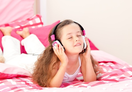 beautiful bed: Beautiful little girl listening music lying on her bed  Stock Photo
